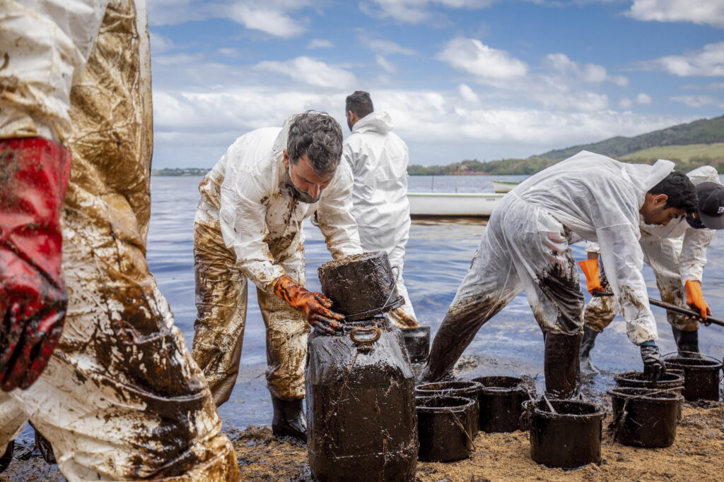 Vrijwilligers, bedekt in olie, proberen hun steentje bij te dragen.
