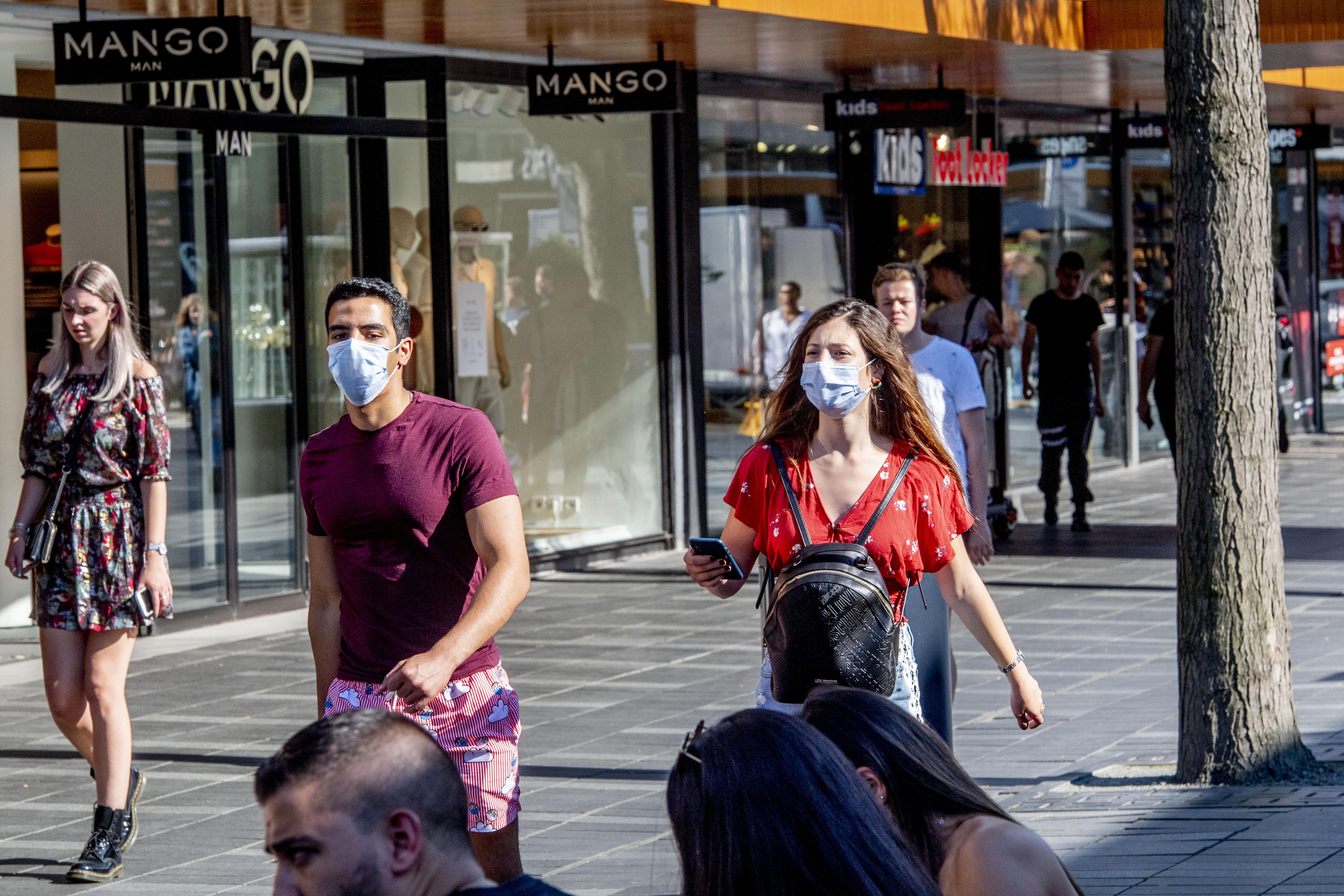 Een foto van mensen met een mondkapje op de Lijnbaan in Rotterdam