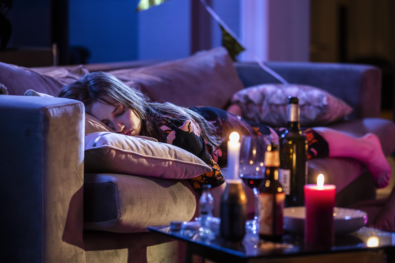 Een foto van Barbara Sloesen als Iris tussen drankflessen op de bank