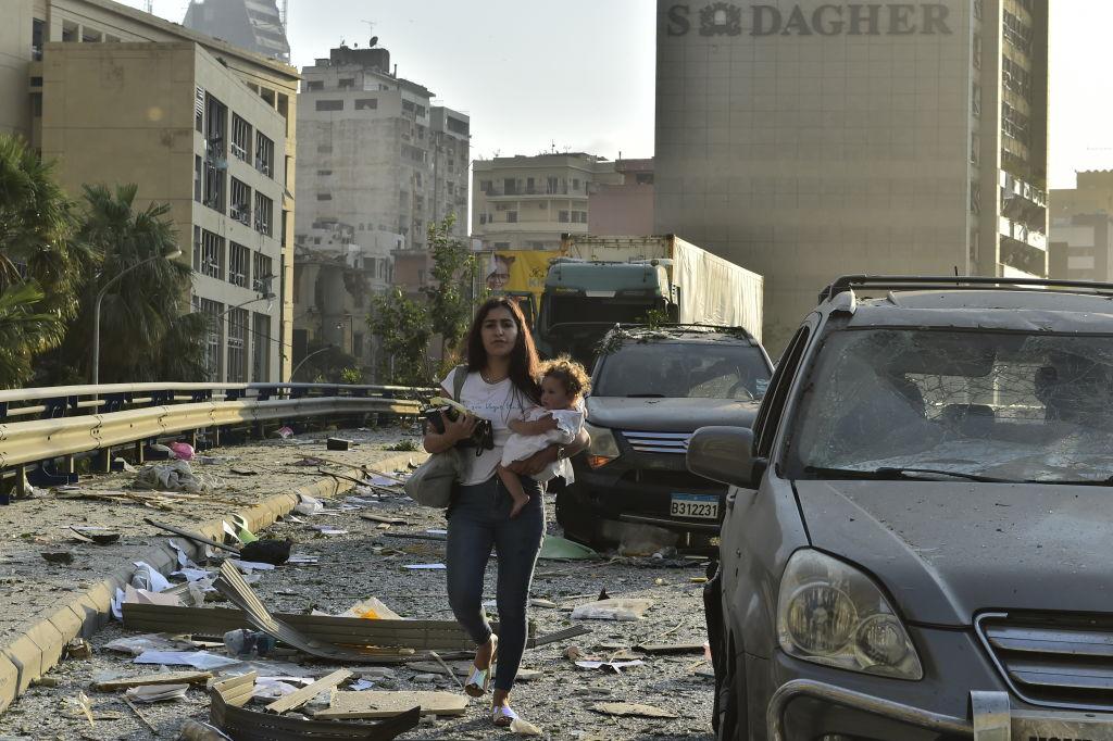 Een foto van een vrouw met haar kinder in het puin van Beiroet