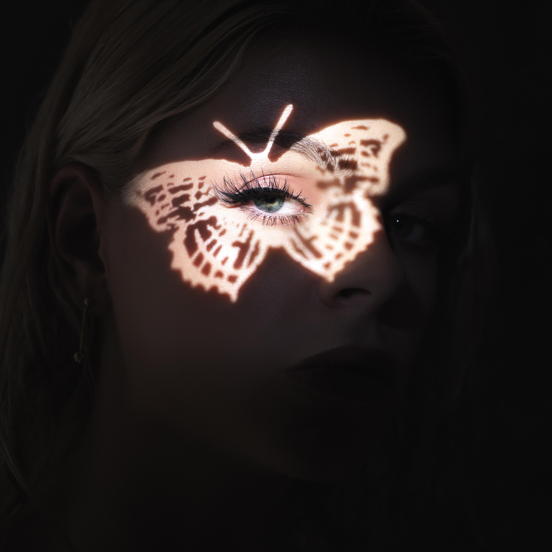 Een foto van de cover van my own world van Davina Michelle. Haar gezicht is verlicht met een vlinder