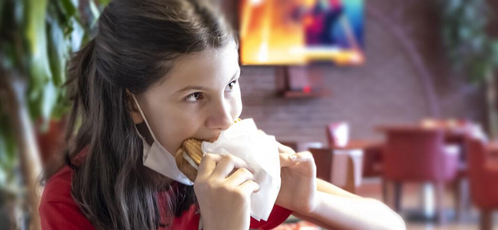 Op deze foto zie je een meisje een tosti eten met haar mondkapje nog om