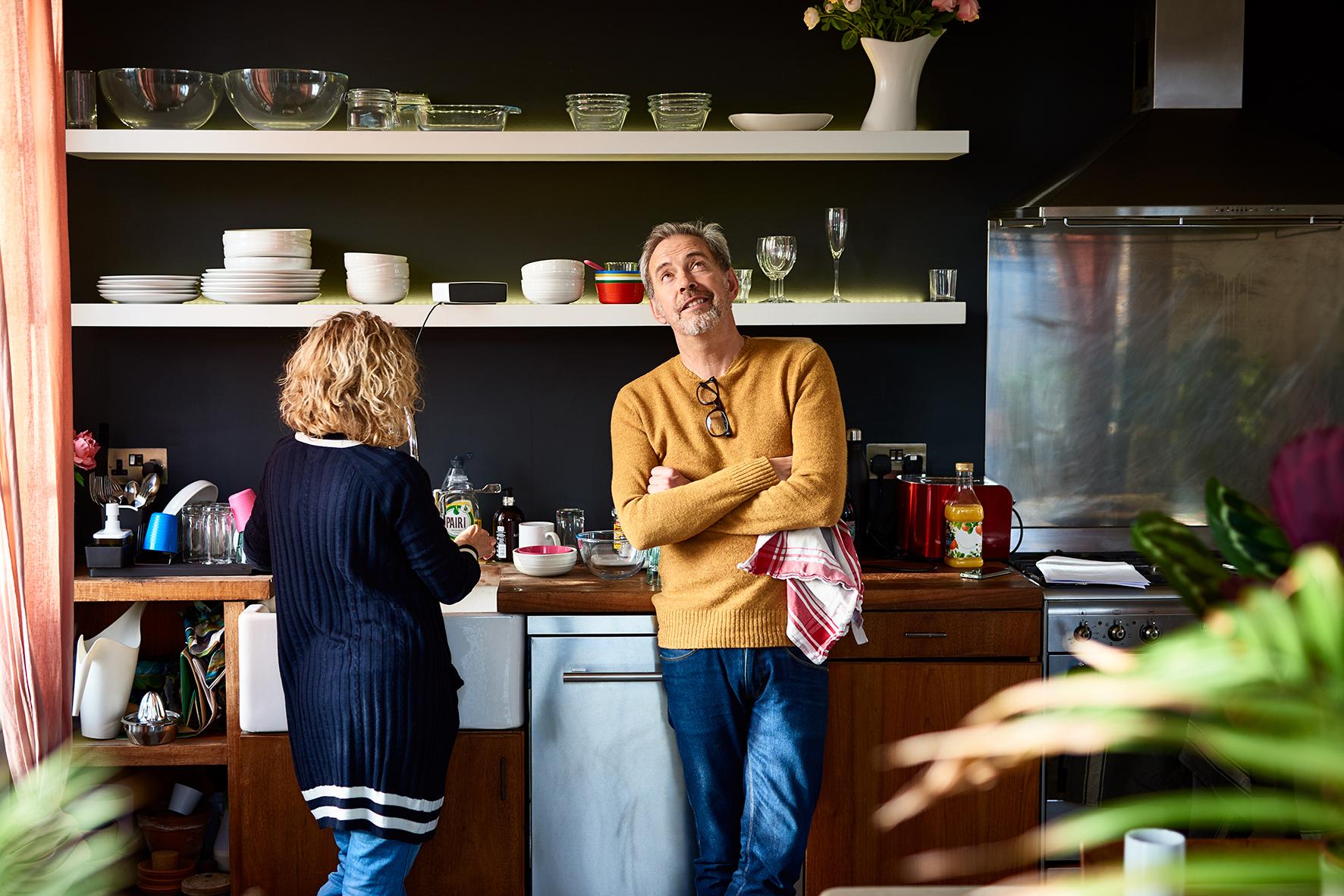 Op deze foto zie je een man tegen het aanrecht aanleunen tijdens de afwas