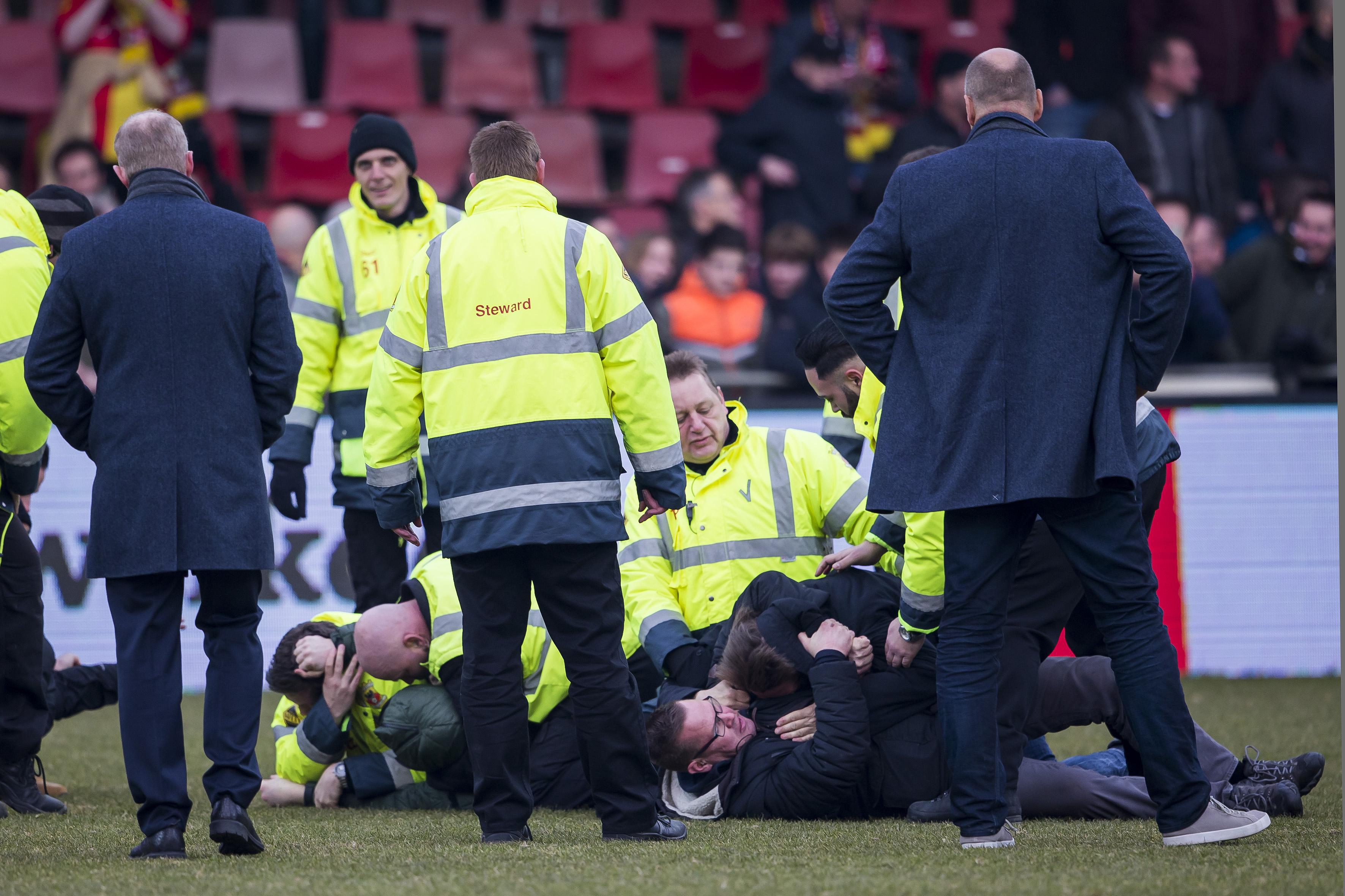 Een foto van beveiligers die supporters van Go Ahead Eagles op het veld overmeesteren