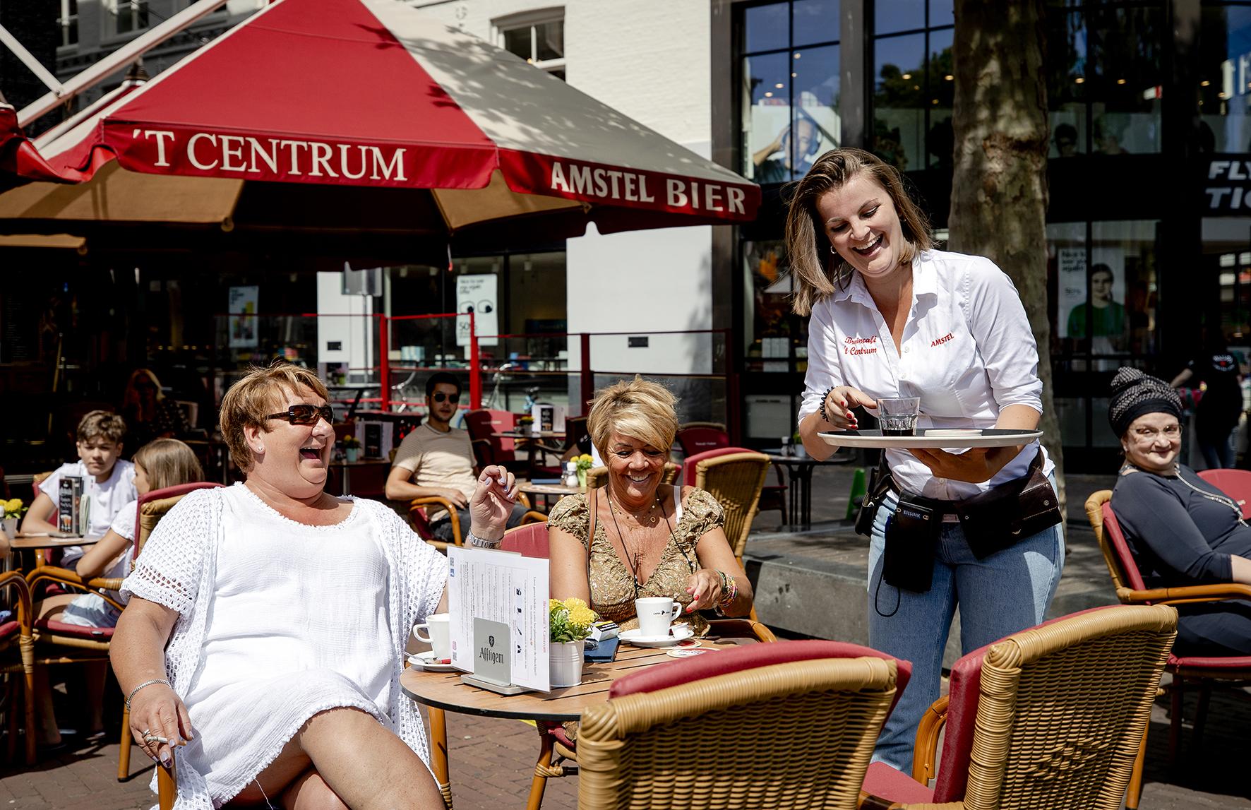 Op deze foto zie je mensen op een terrasje zitten op het Rembrandtplein in Amsterdam