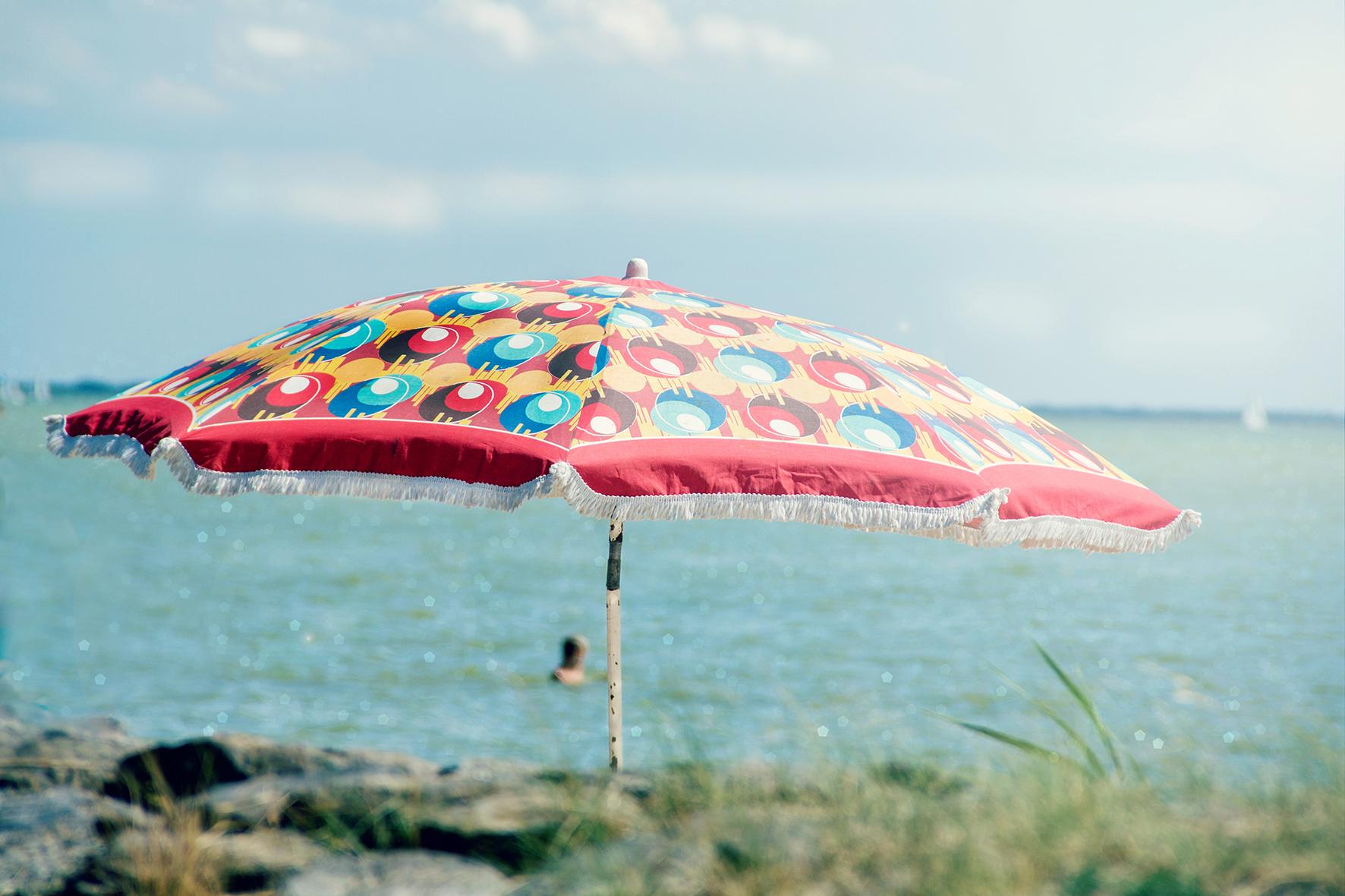 Op deze foto zie je een parasol en iemand lekker in het IJsselmeer zwemmen