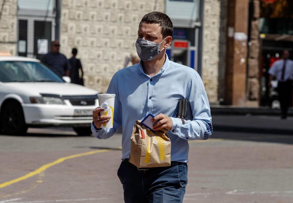 Een foto van man met eten en een milkshake van McDonald's in zijn handen