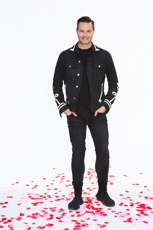 Een foto van Fred van Leer, staand op rozenblaadjes