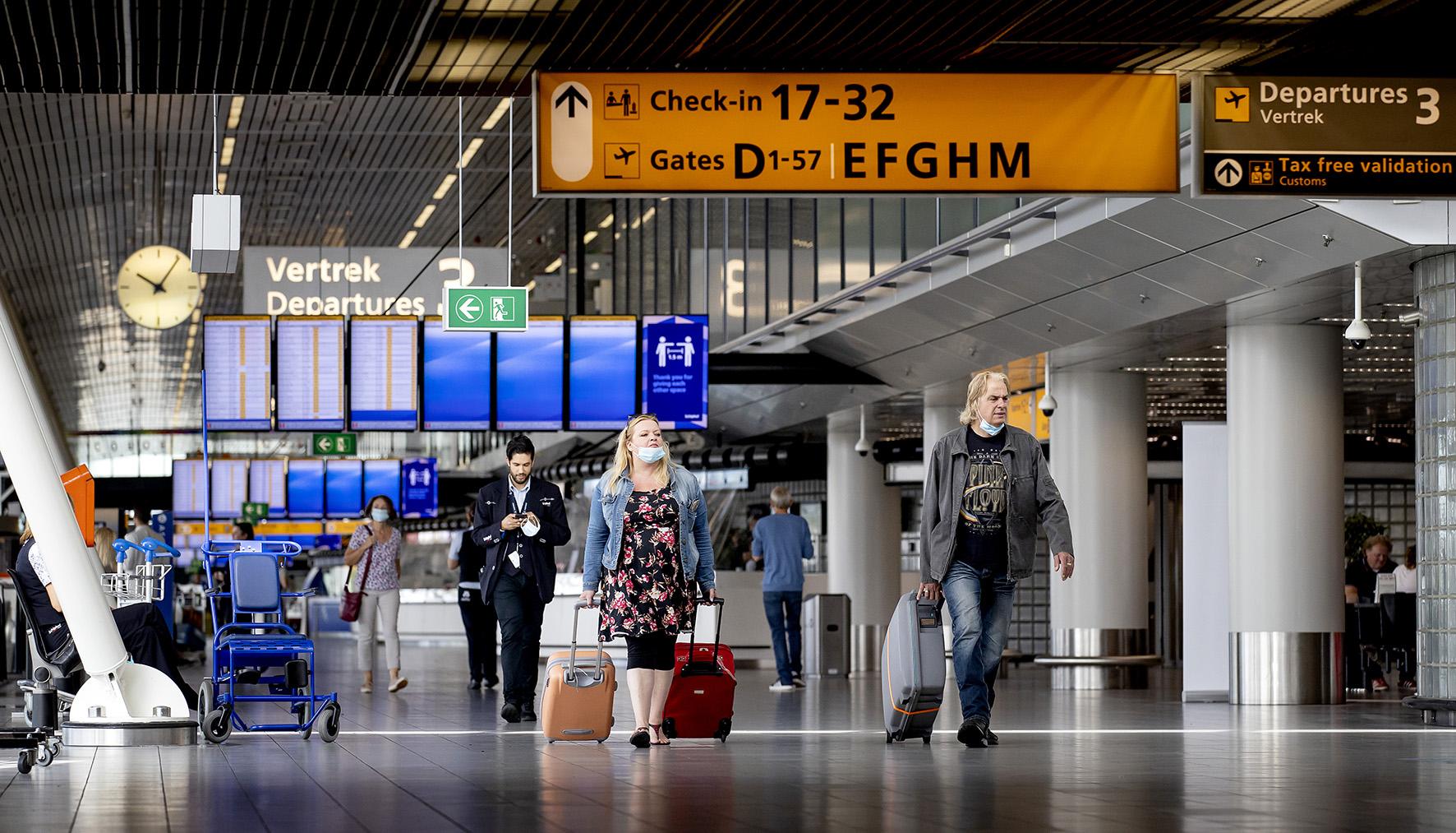 Op deze foto zie je reizigers op luchthaven Schiphol. Het aantal vluchten is toegenomen, sinds er meer Europese landen toegankelijk zijn voor Nederlanders.