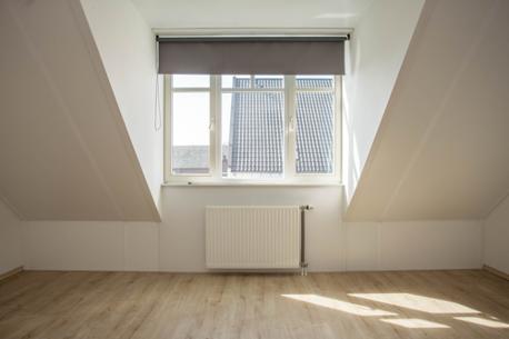 Een foto van een lege slaapkamer met een dakkapel