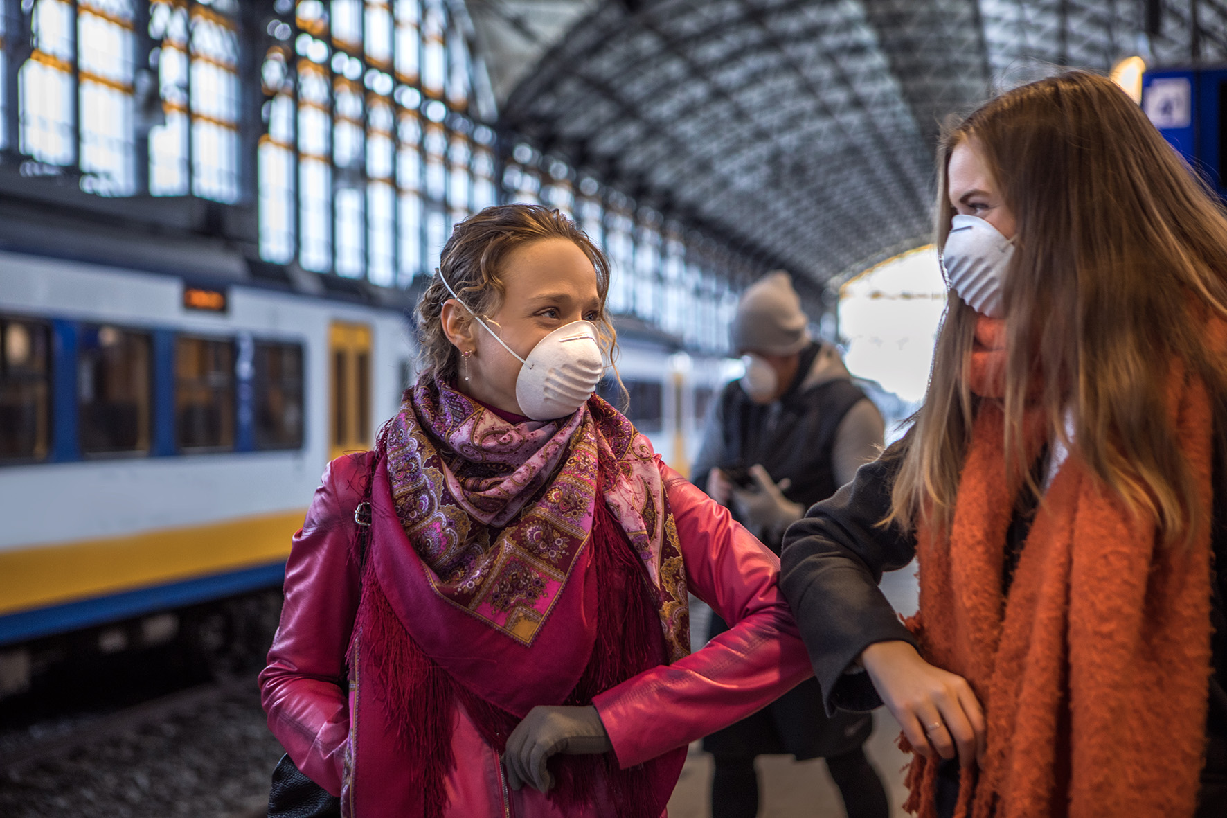 Vriendinnen op het station met mondmaskers