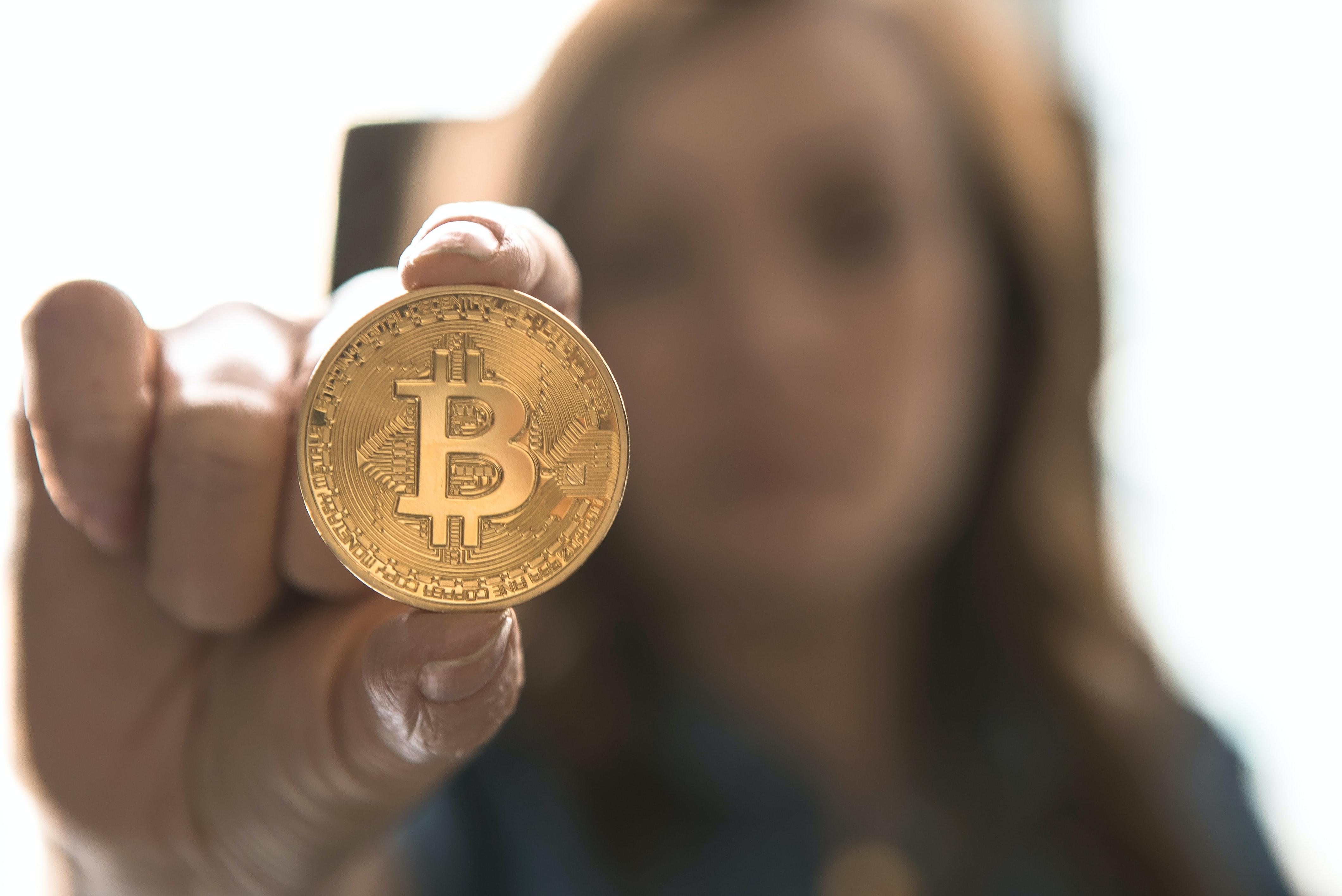 Een foto van een dame met een bitcoin tussen haar vingers