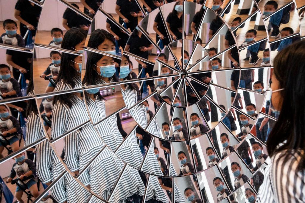 Een foto van het Sciene Museum in Londen waarbij een meisje met een mondkapje zichzelf in talloze spiegels ziet