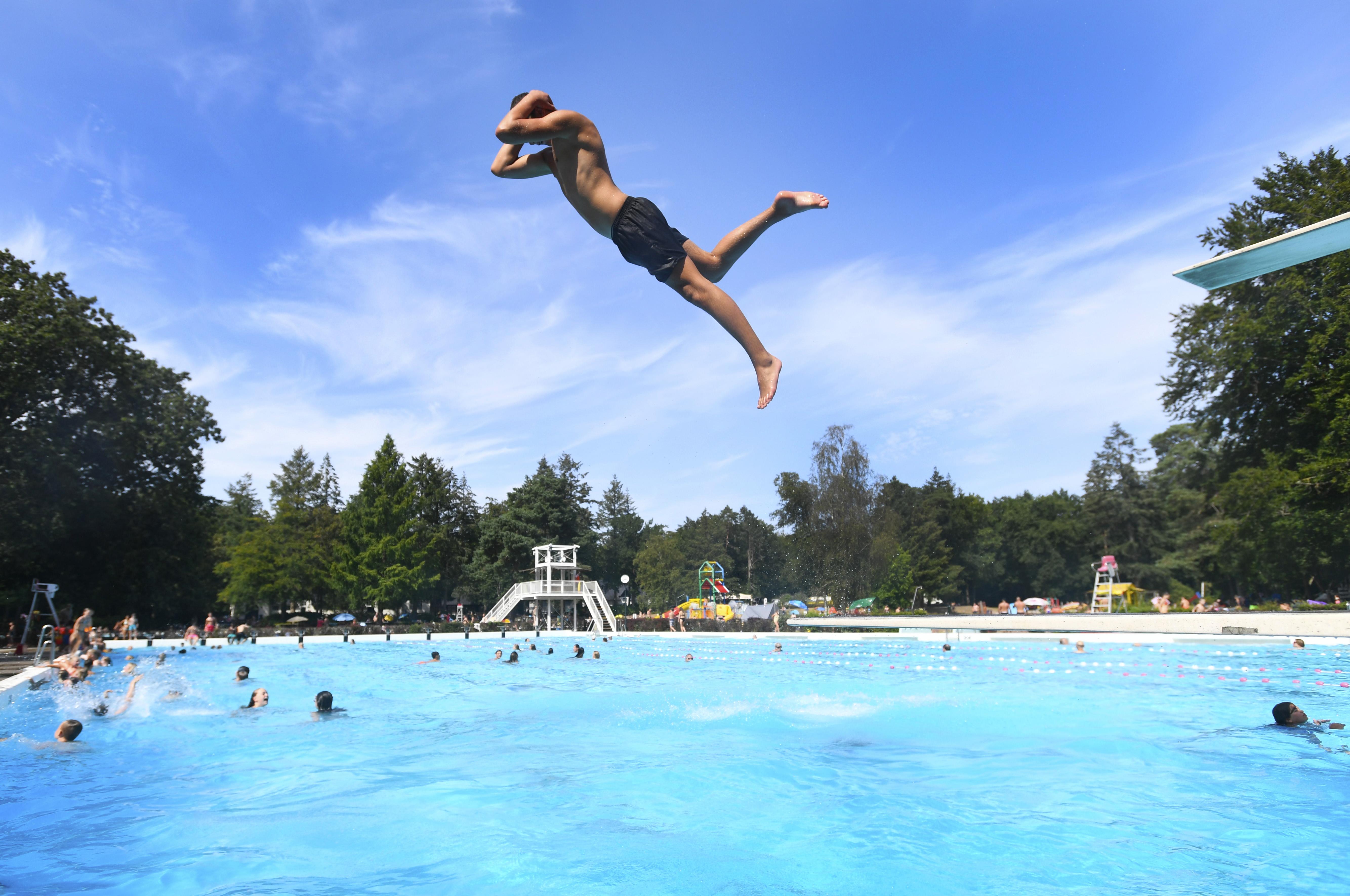 Een foto van een man die van de duikplank in een zwembad springt.