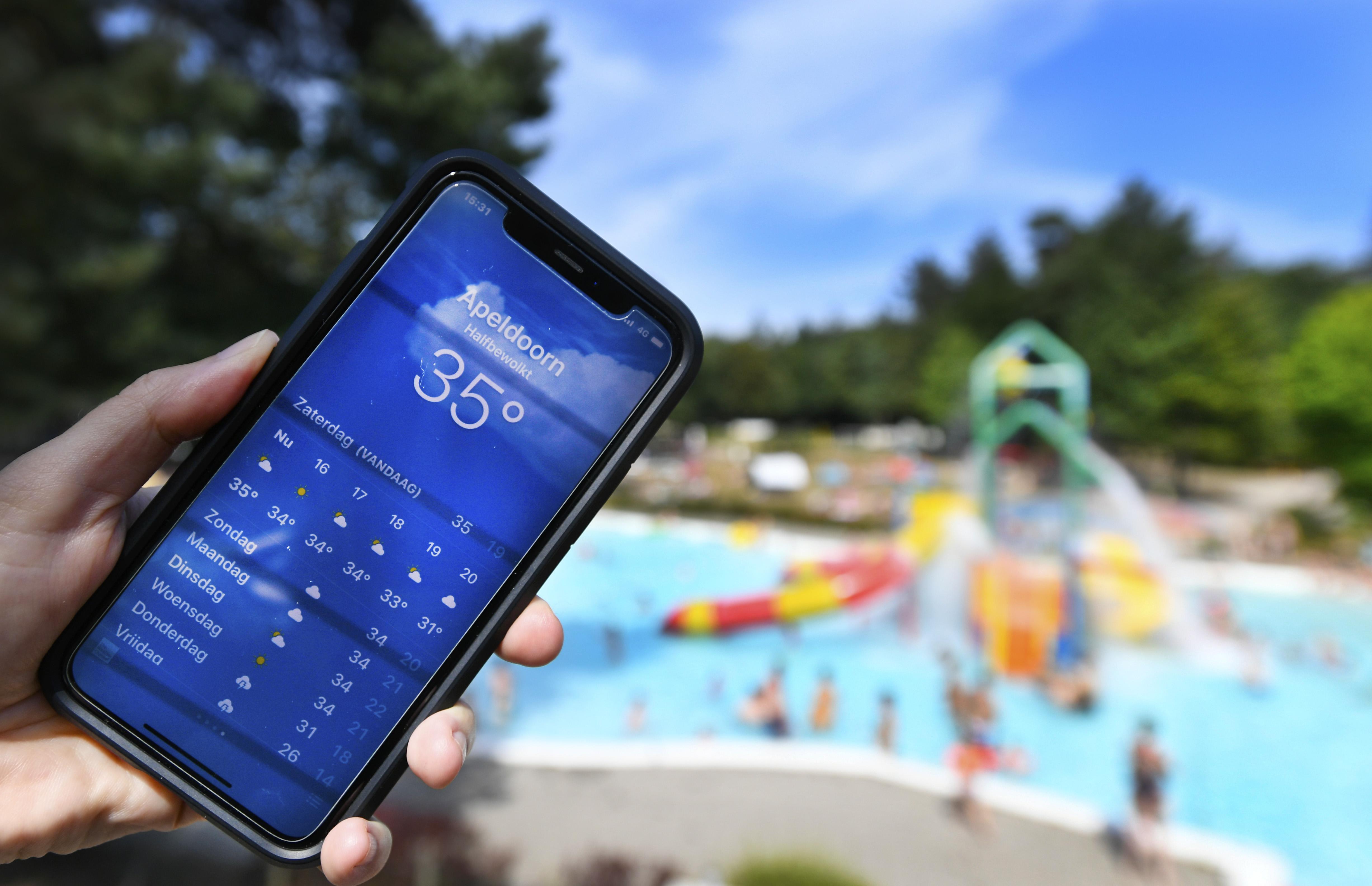 Een foto van een smartphone waarop staat dat het 35 graden is