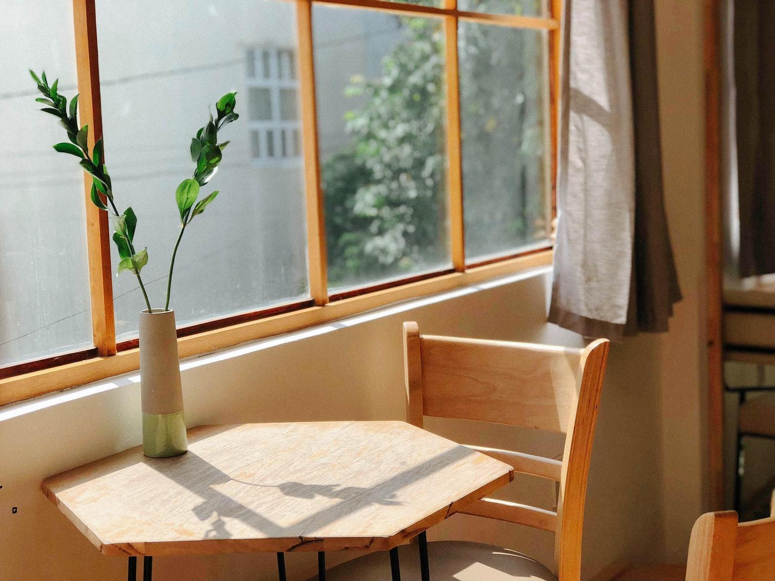 Op deze foto is een plant op een bruin tafeltje te zien.
