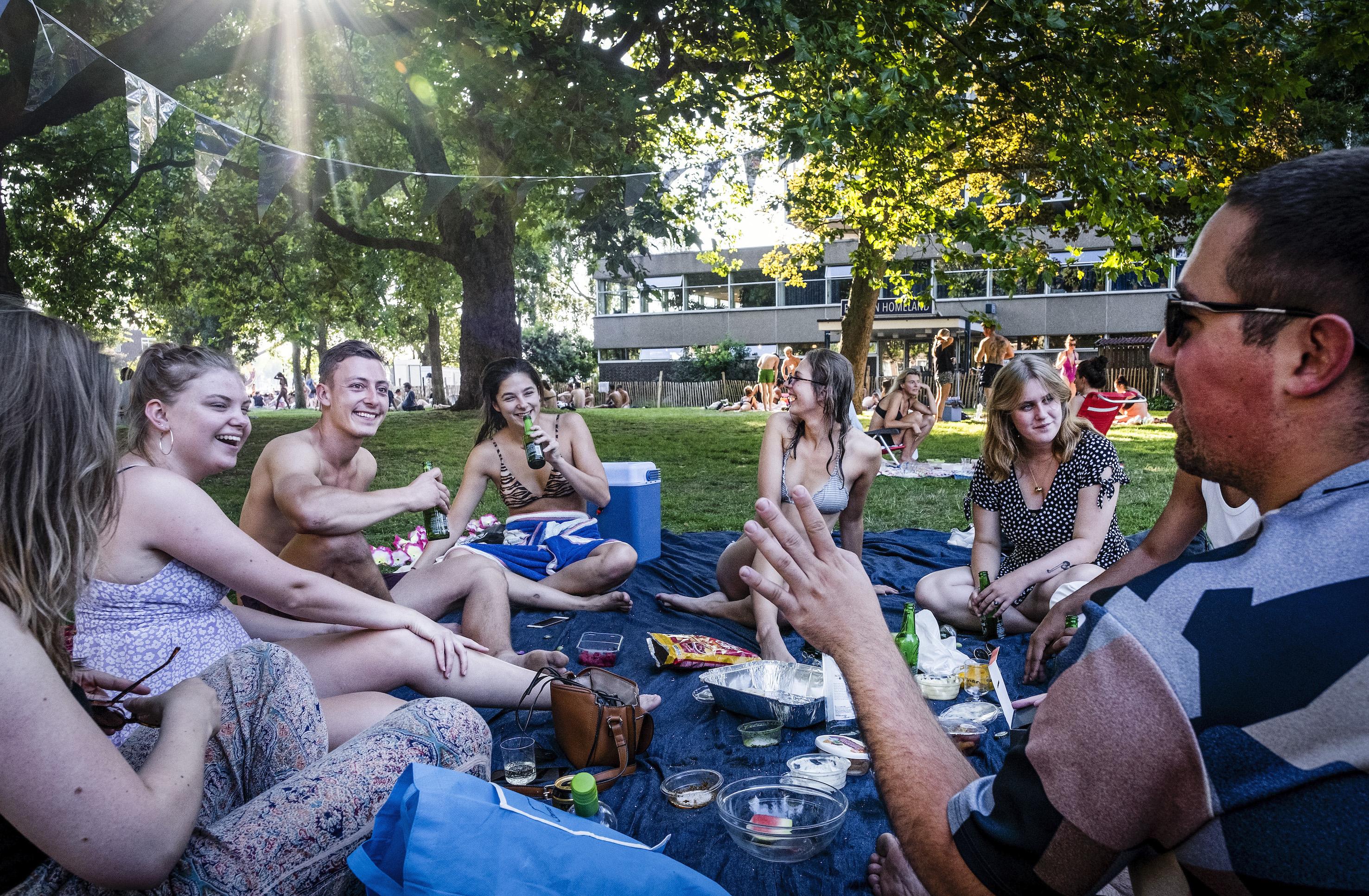 Een foto van borrelende mensen in een park.