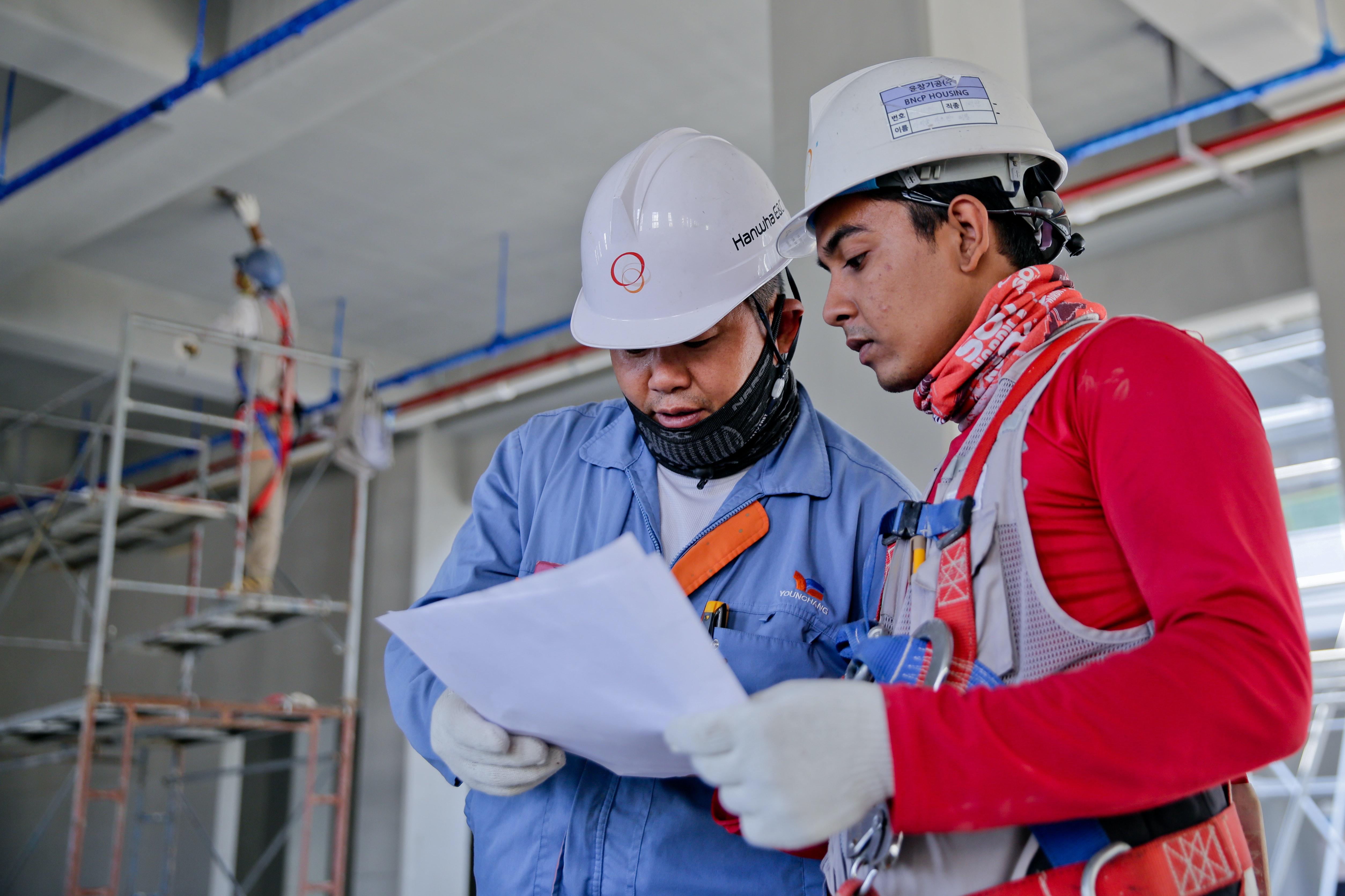 Een foto van werknemers die veilig werken met helmen