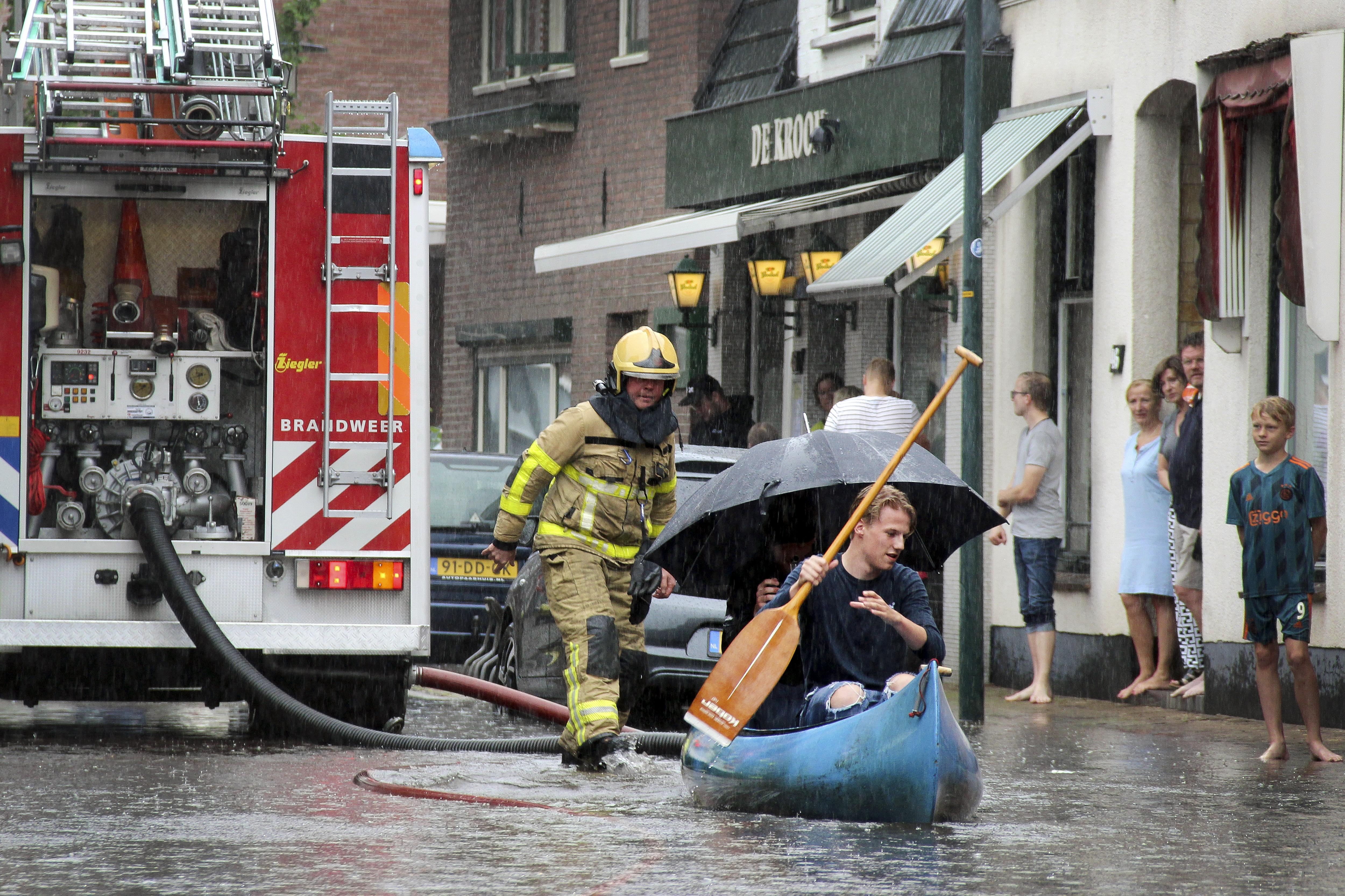 Een foto van een man die vaart door het water in een straat.