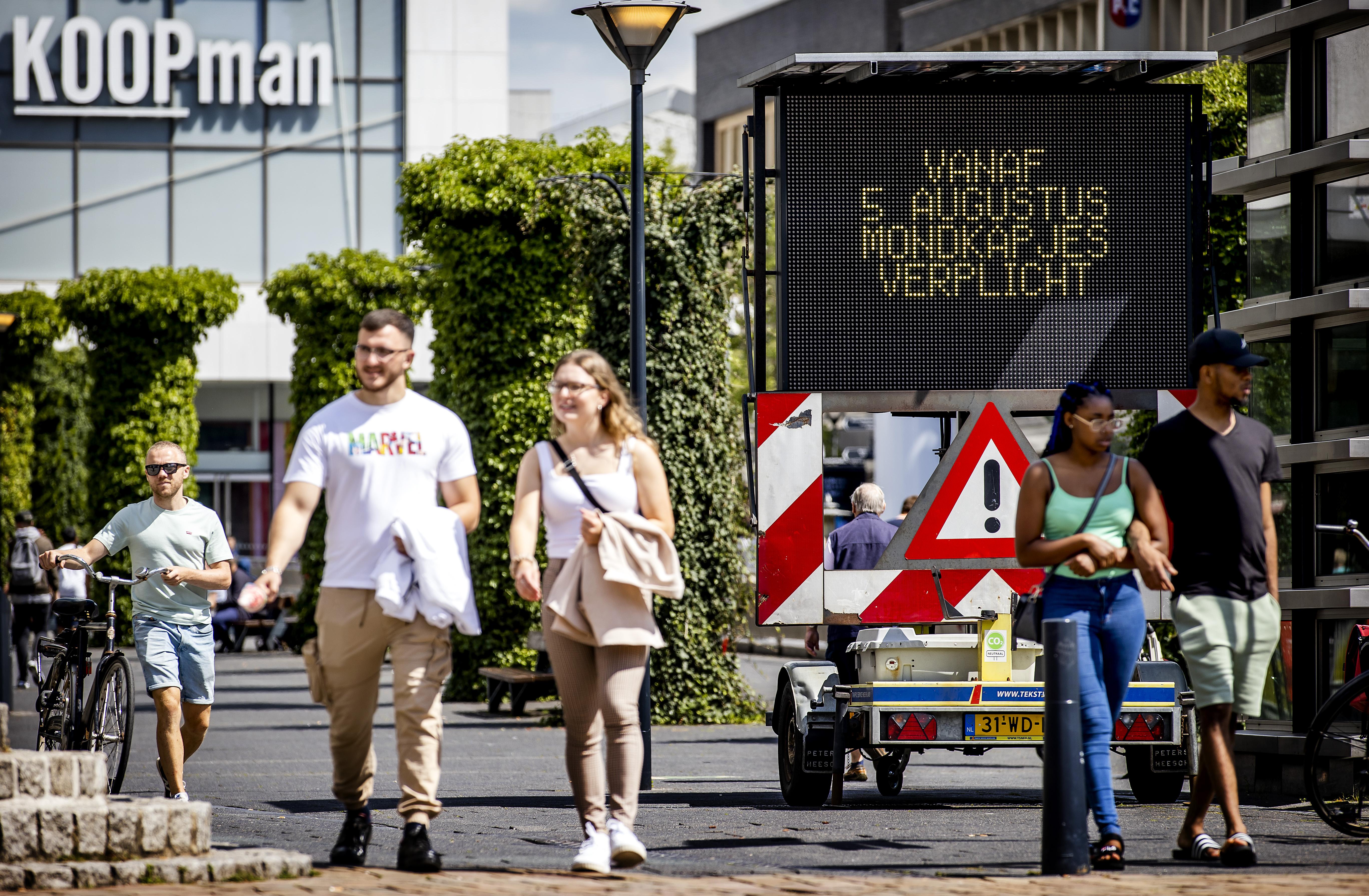 Een foto van een bord waarop staat dat een mondkapje in de Rotterdamse Koopgoot vanaf morgen verplicht is