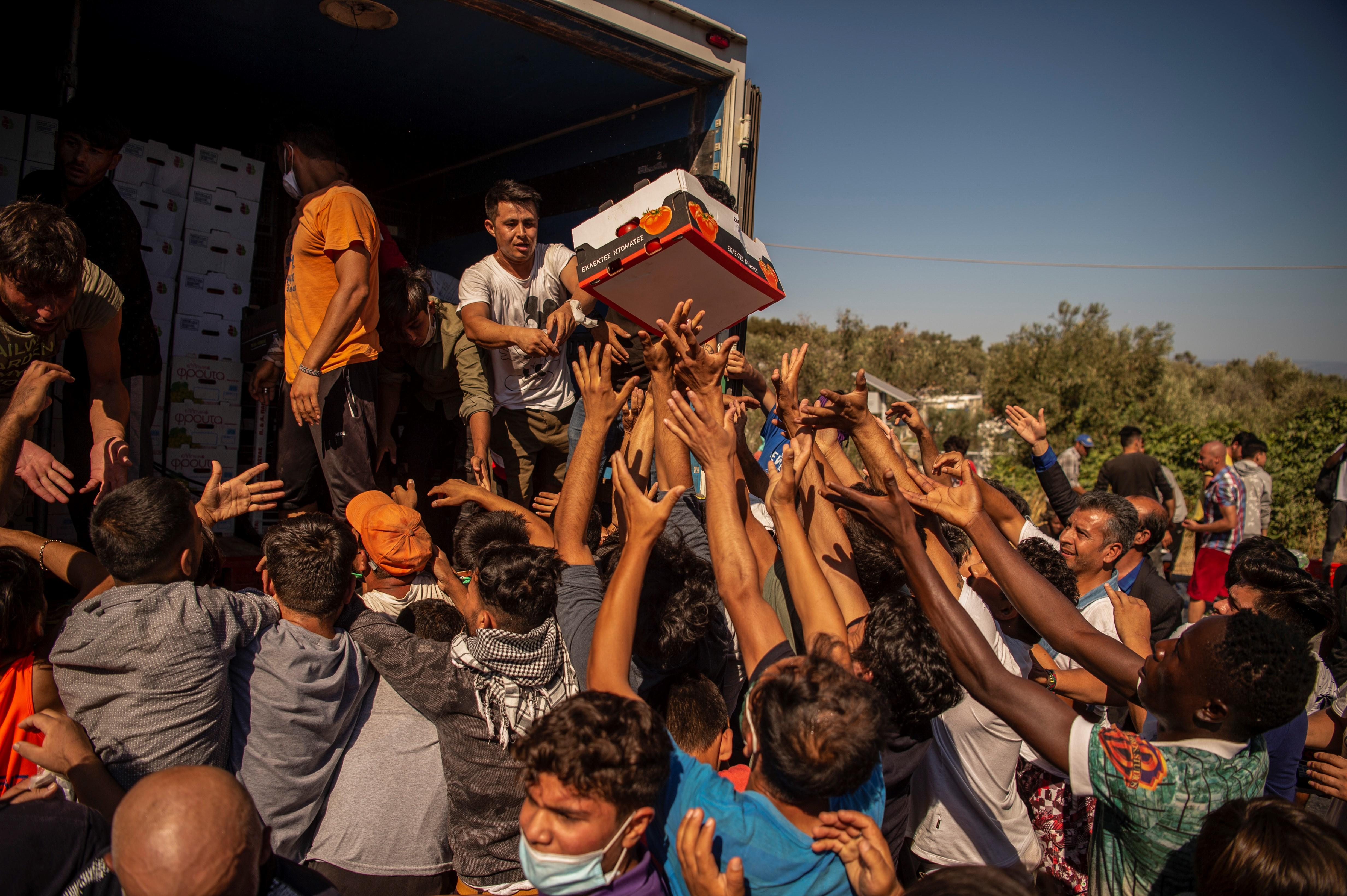 Migranten uit Moria tijdens het uitdelen van eten nadat het kamp werd verwoest