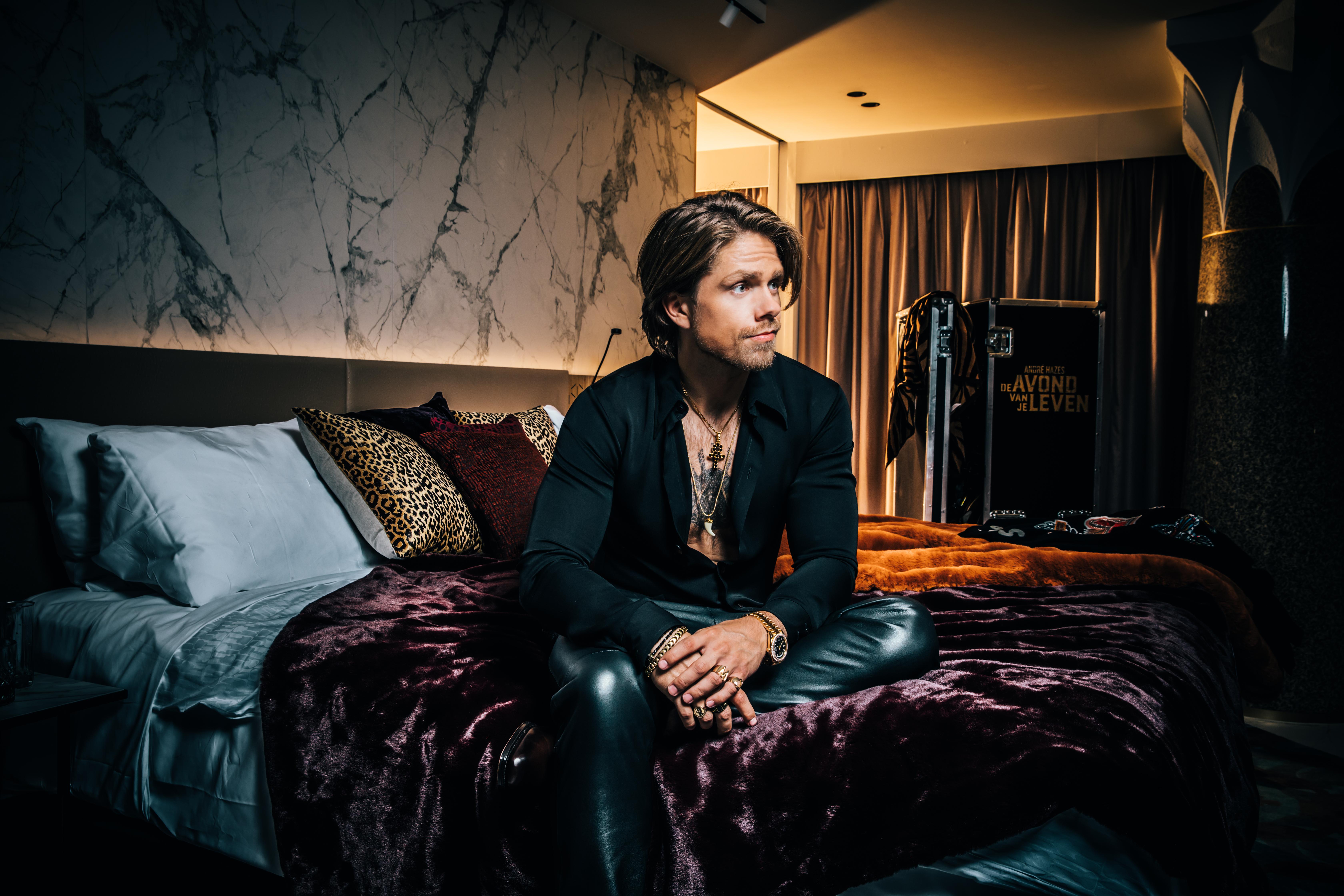 Een foto van André Hazes op een bed