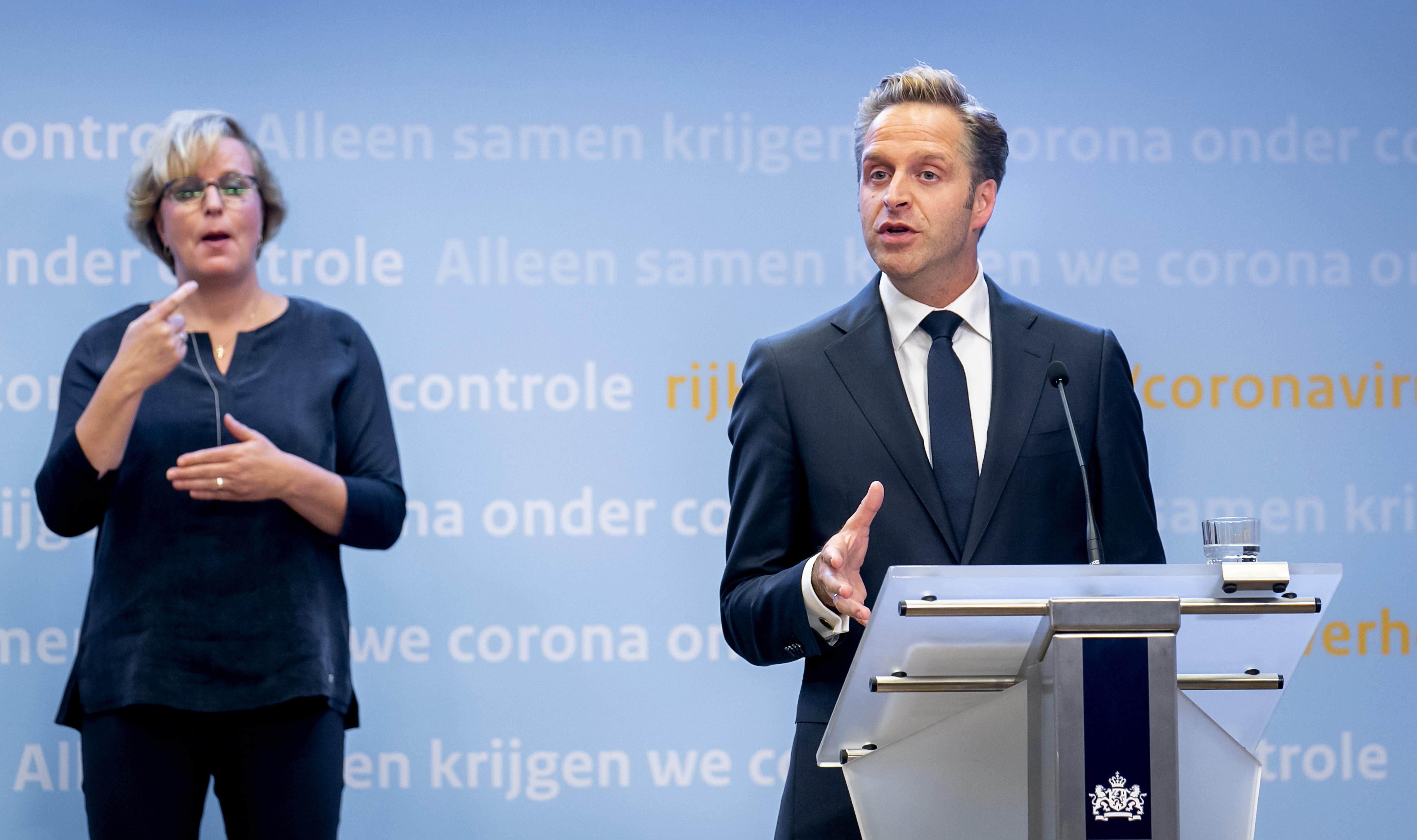 Een foto van Hugo de Jonge en een tolk tijdens de persconferentie