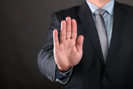 Een foto van een hand met het gebaar 'nee, stop'