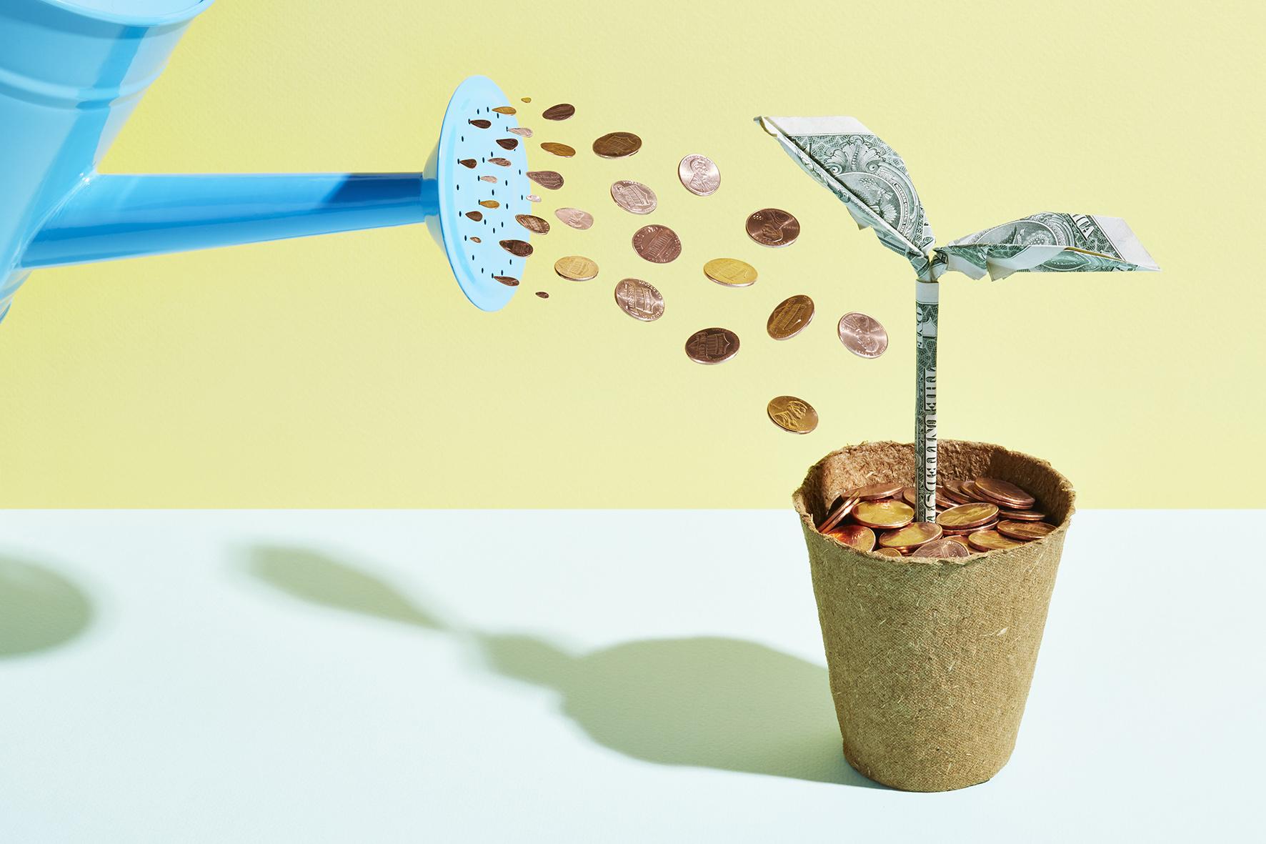 Iemand geeft een origamiboompje water met geld
