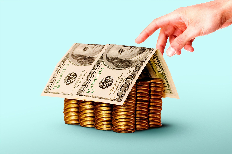 Een foto van briefjes geld op muntgeld, in de vorm van een huis