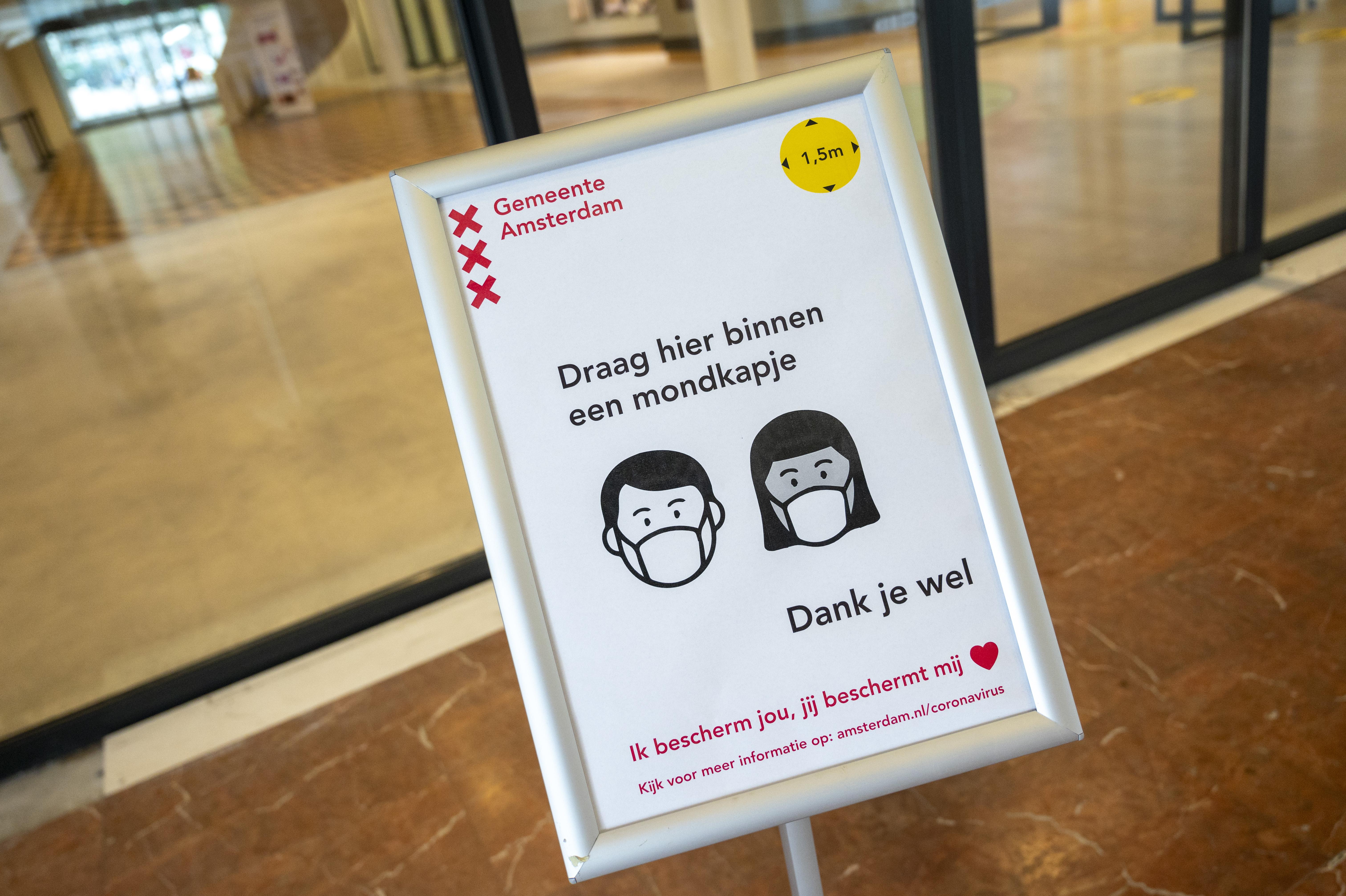 Een foto van een bord over het dragen van een mondkapje bij de gemeente Amsterdam