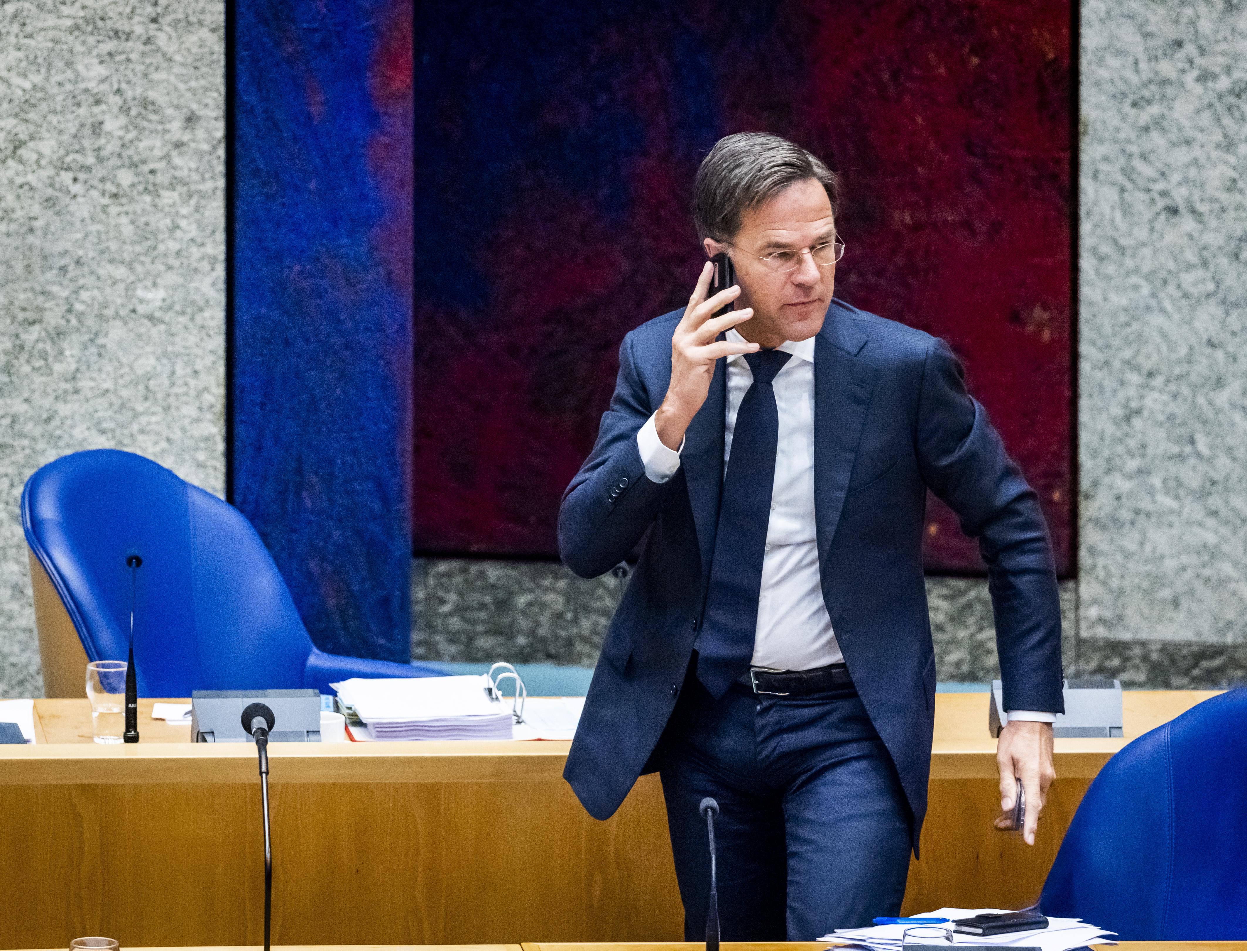Een foto van premier Rutte, bellend tijdens een schorsing van het debat over het dragen van een mondkapje