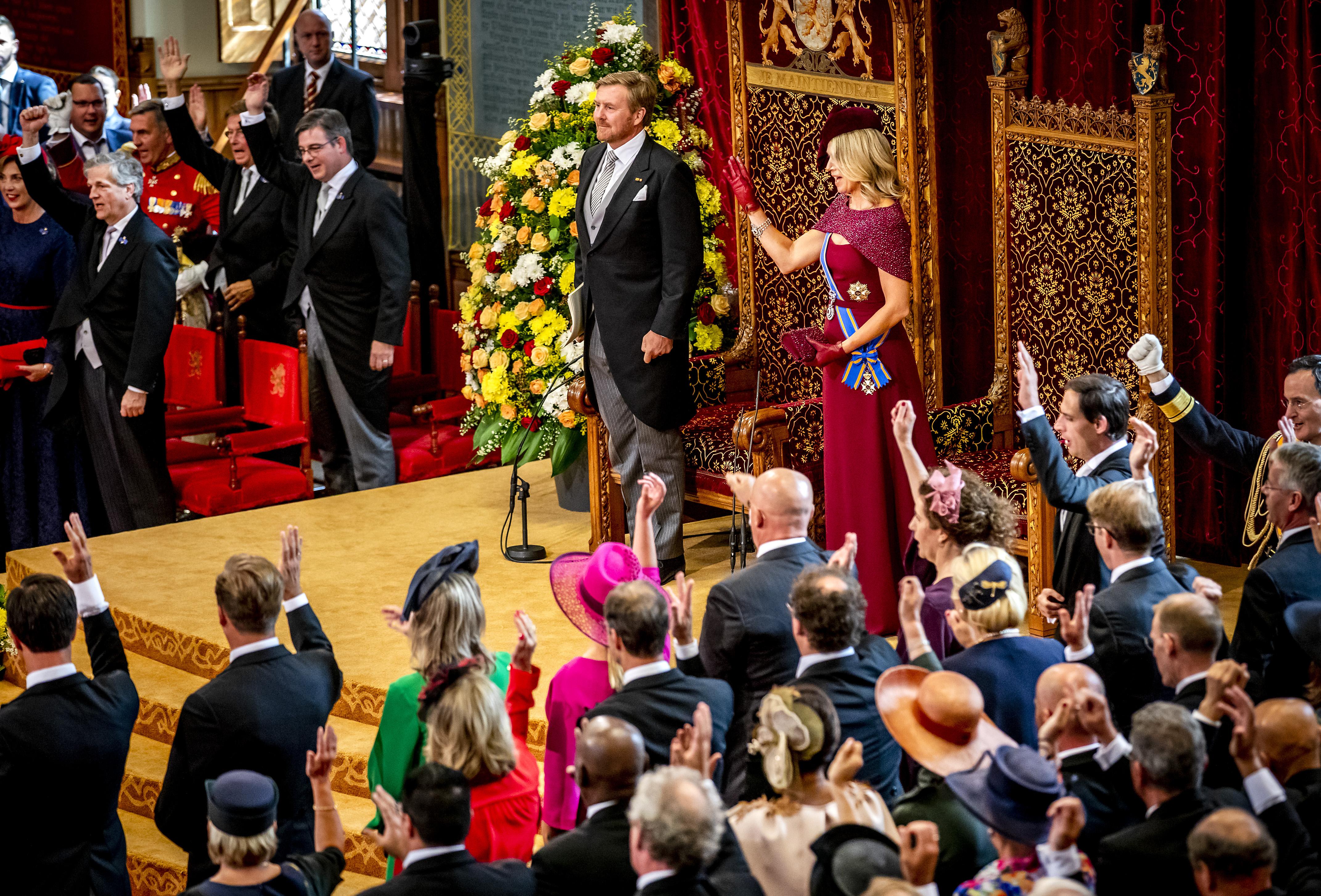 Op deze foto is een moment tijdens Prinsjesdag 2019 te zien, de koning en koningin staan, het is druk in de zaal.