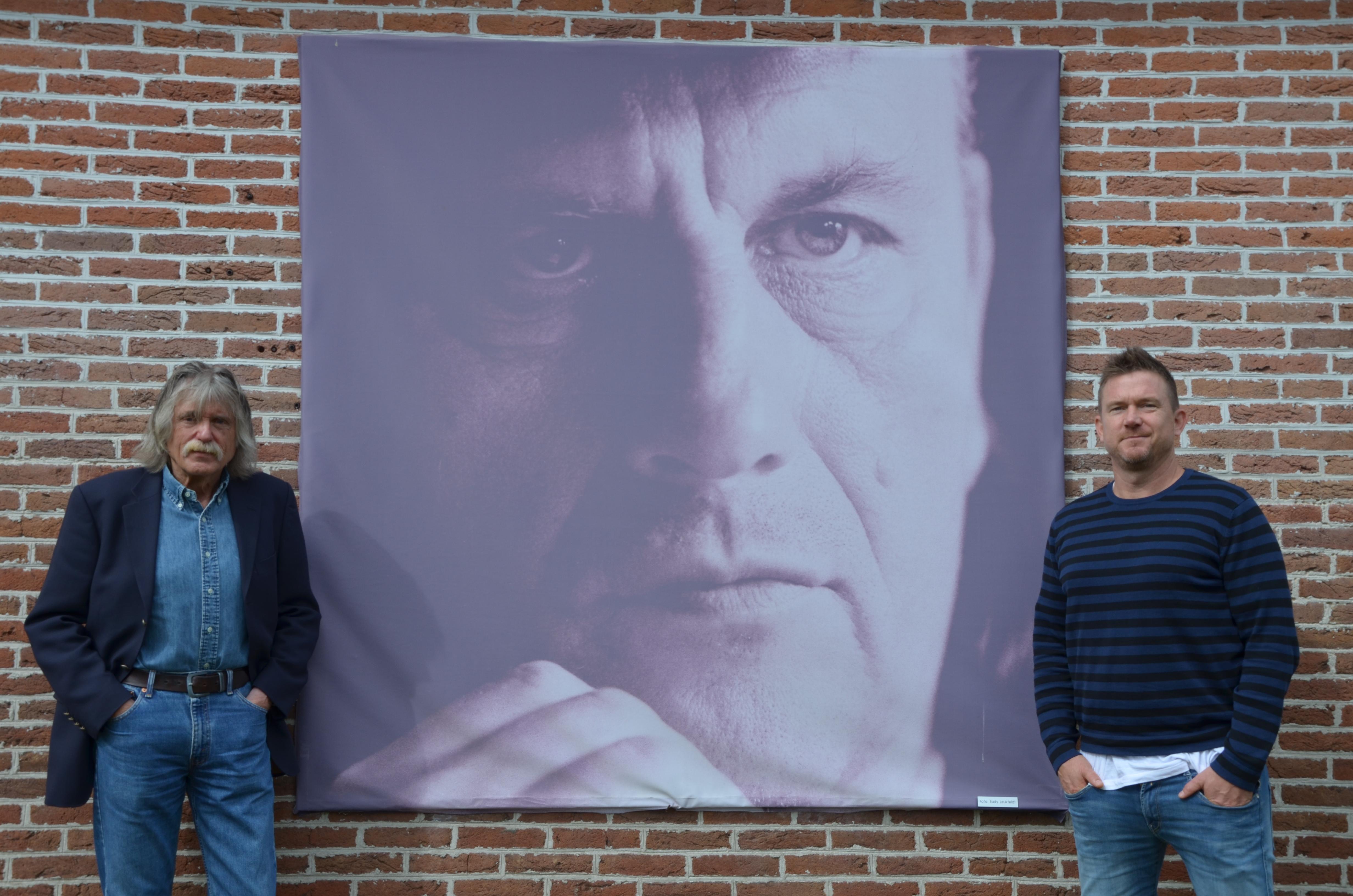Een foto van Johnny de Mol met Johan Derksen bij een afbeelding van Harry Muskee in Grolloo