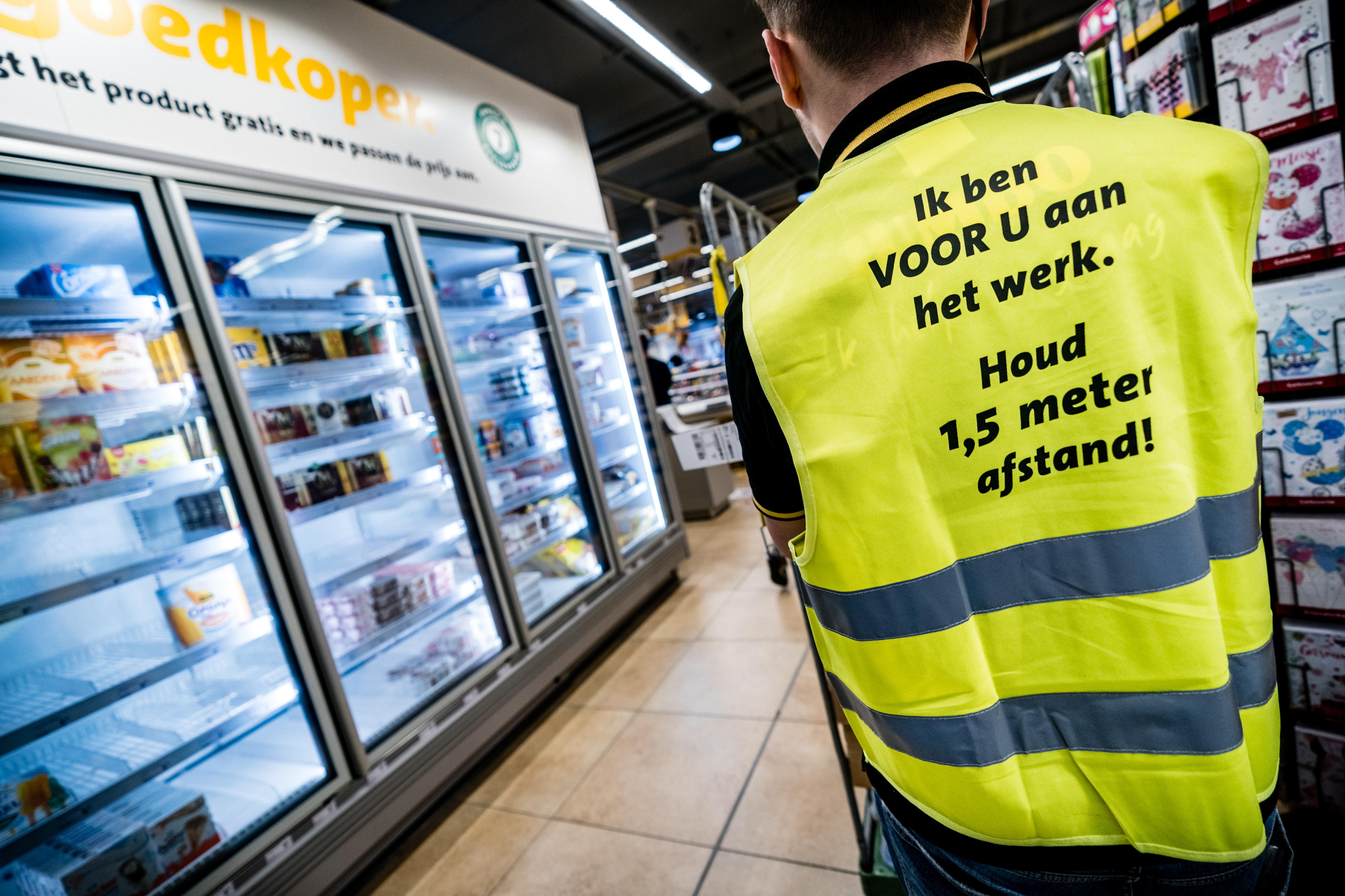Een foto van een supermarktmedewerker die er voor zorgt dat je veilig boodschappen kunt doen
