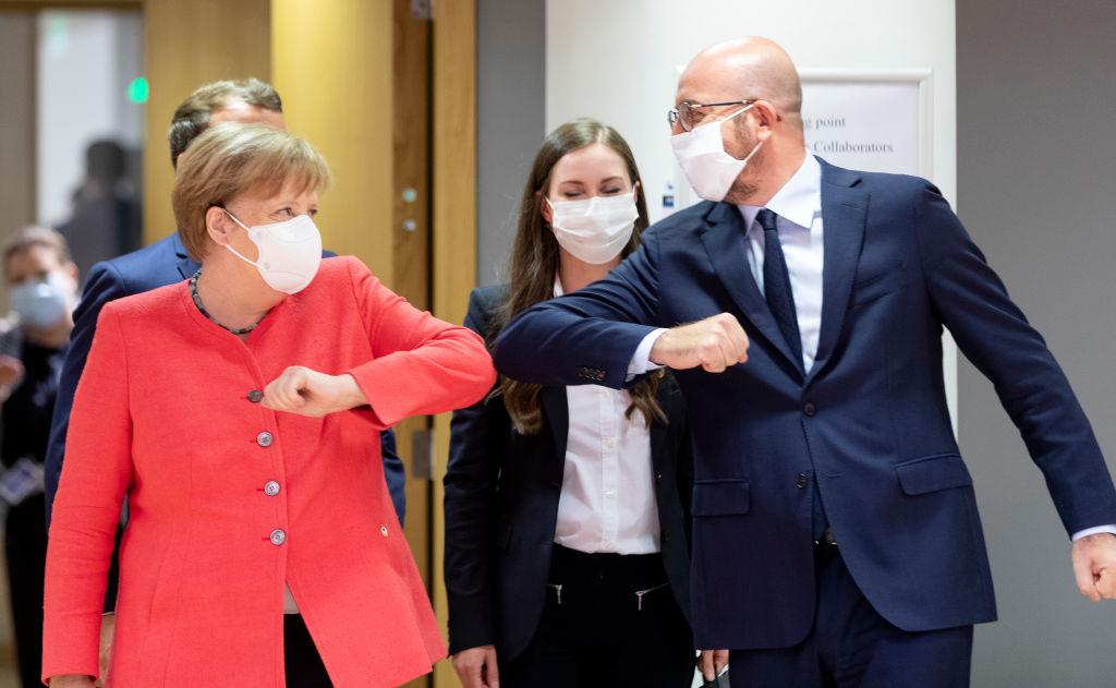Een foto van Angela Merkel met een mondkapje en een elleboog als groet