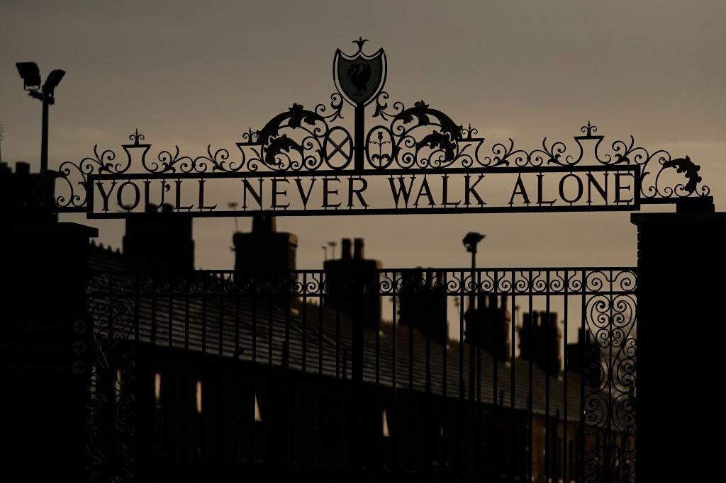 Een foto van een You Never Walk Alone-poort in de duisternis, passend bij de coronamaatregelen in Liverpool