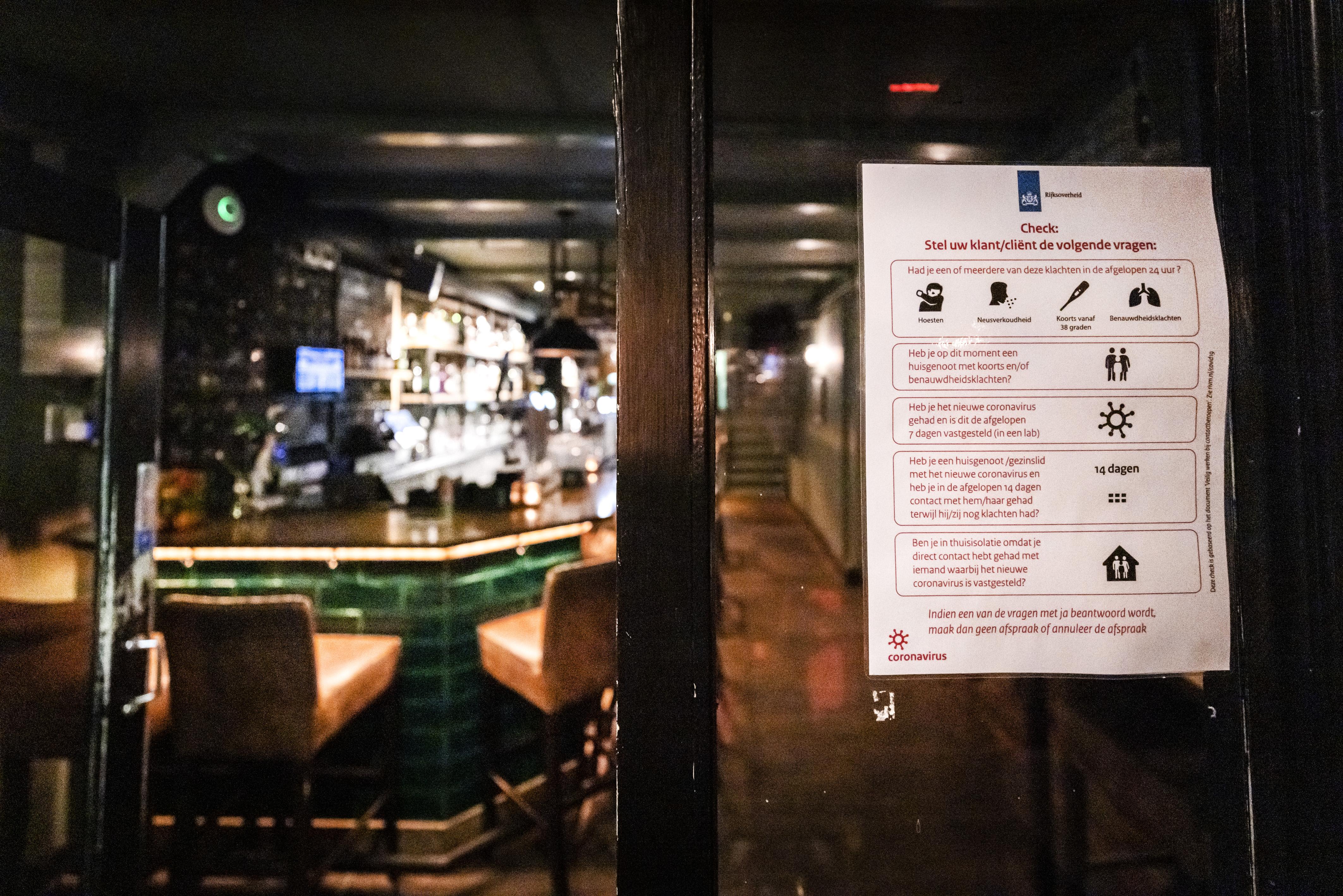 Een foto van een lijst aan het raam met coronamaatregelen in een café