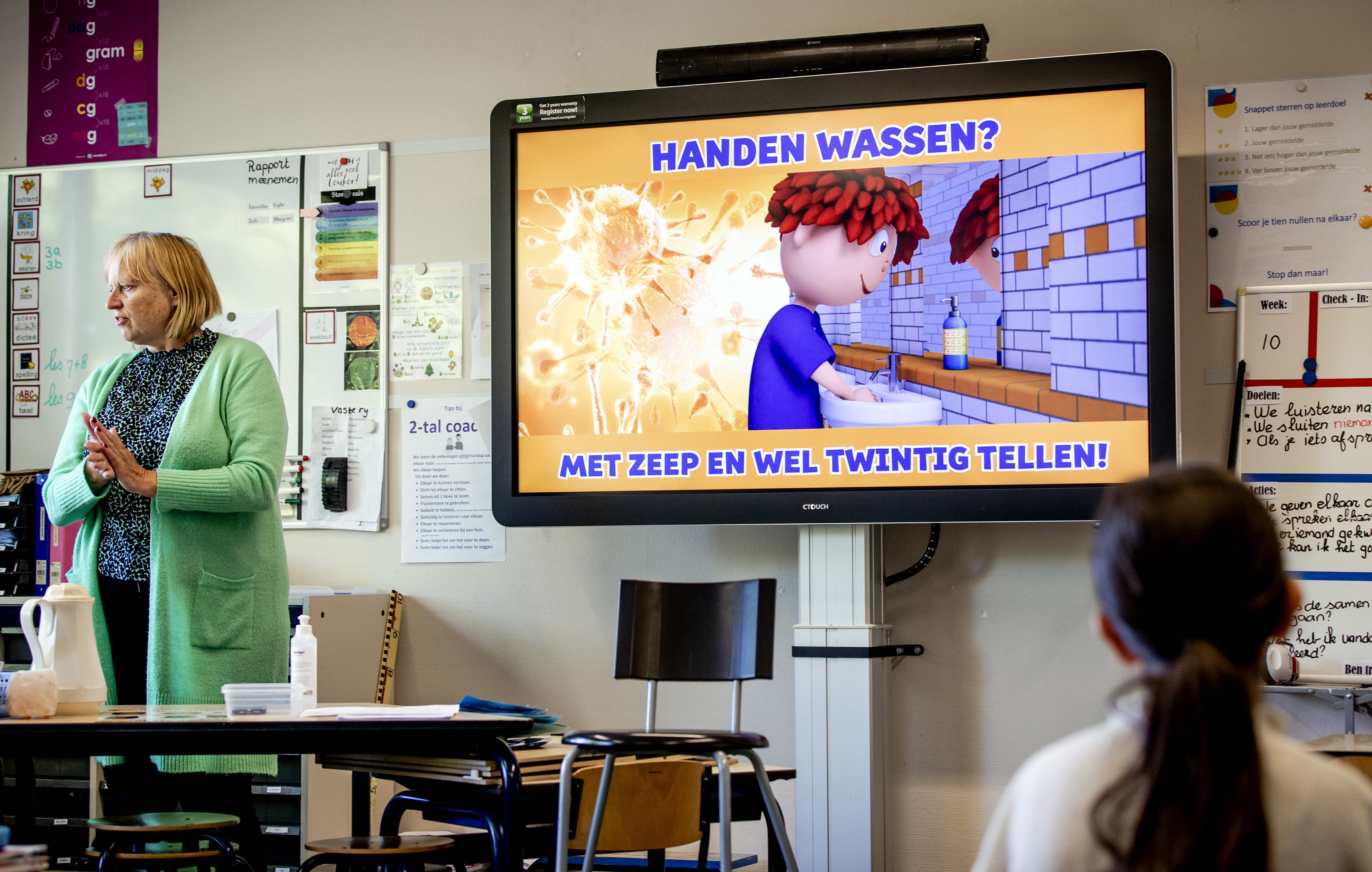 Een foto van een schoolklas die informatie over handen wassen krijgt
