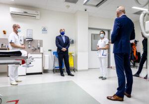 Een foto van de koning die aandachtig luistert naar ziekenhuispersoneel en Ernst Kuipers