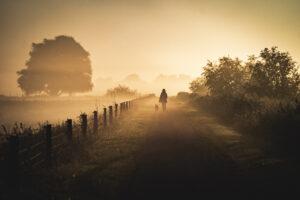 Een foto van een vrouw die wandelt in de mist bij een opkomende zon