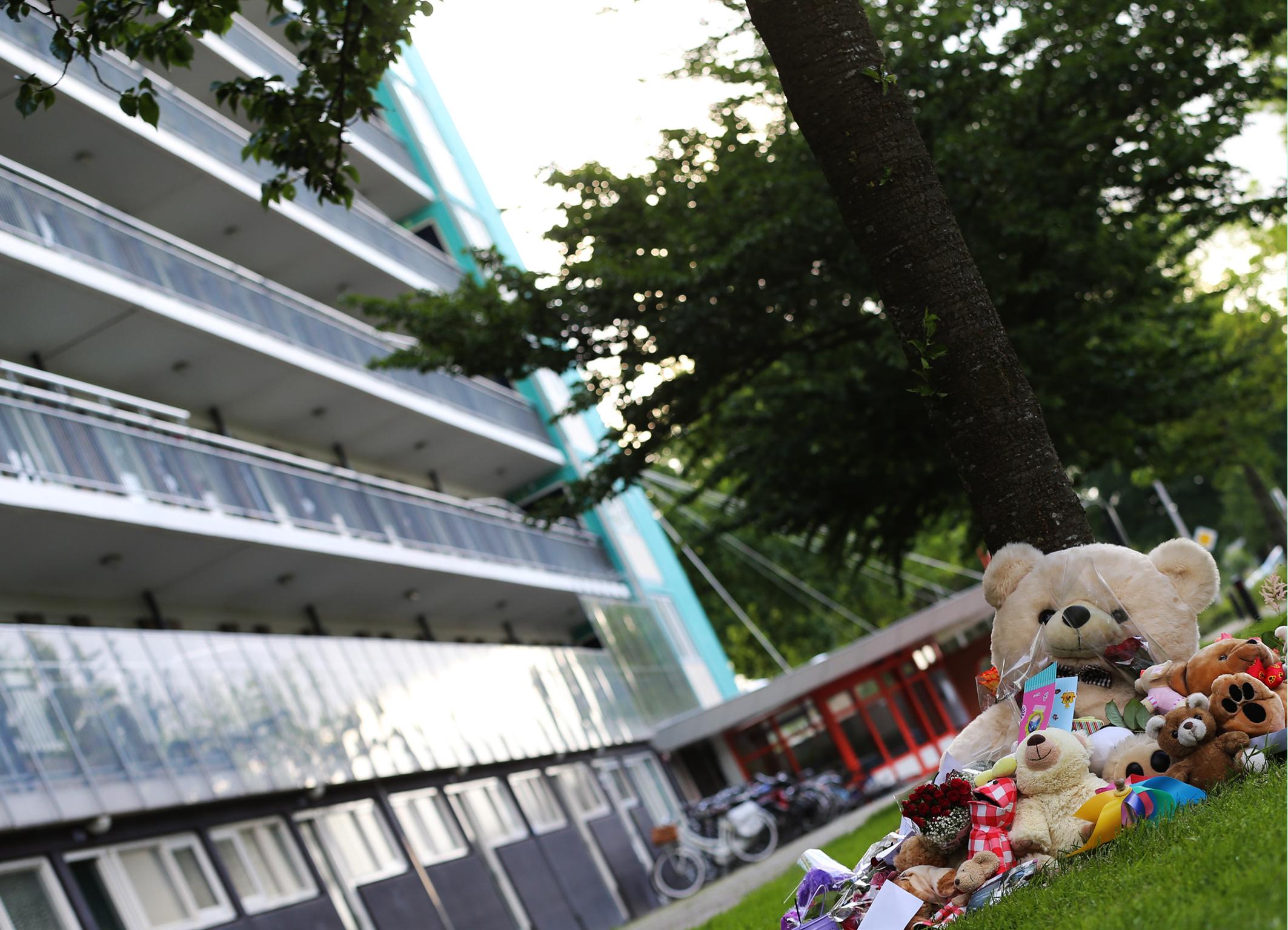 Bloemen en knuffels liggen op de plek onderaan de flat waar het levenloze lichaam van het achtjarige meisje Sharleyne werd aangetroffen.